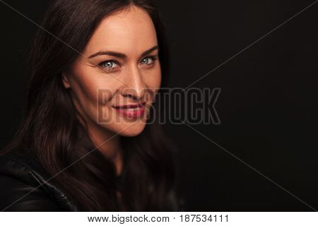 happy woman smiling at the camera on black background with copyspace