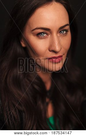 portrait of a young woman with blue eyes on black studio background