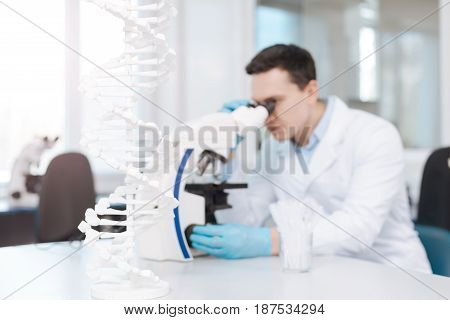My job. Concentrated scientist using microscope while testing mutation of genes, sitting at his workplace on the background