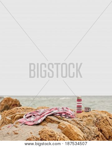 Pink plaid in a cage and a thermos with a cup on a stone on the beach near the sea. Selective focus.