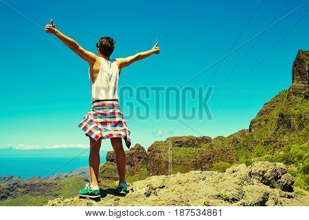 Casual Hipster Clothes Standing On The Cliff Of Mountain With Raised Hands