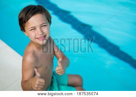 Portrait of smiling boy showing thumbs up at poolside