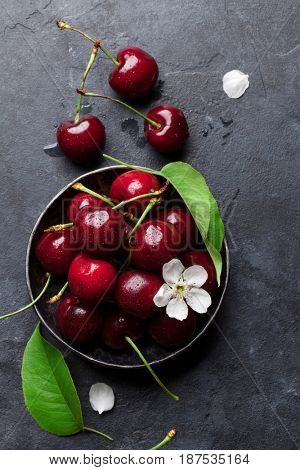 Fresh garden cherry in bowl on stone table. Top view