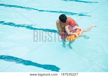 Elevated view of lifeguard rescuing boy from swimming pool