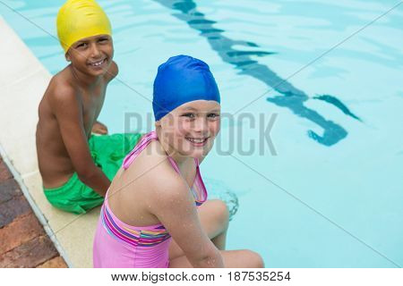 Portrait of smiling kids sitting near poolside at the leisure center