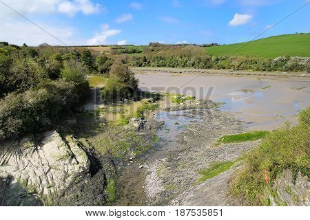 Part Of The Camel Estuary In Cornwall At Low Tide With Green Fields And Blue Sky