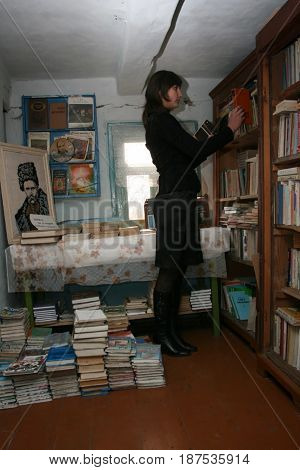 POCHAPY UKRAINE - 03 December 2008: Young unknown woman in the rural library looking at the book