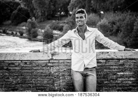Handsome smiling man outdoors. Tiber river from the bridge. A beautiful young Italian man relaxing on Milvian Bridge in the historic center of Rome, Italy. Blue shirt and jeans. Black and white.