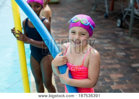 Portrait of little girls with pool noodles at poolside