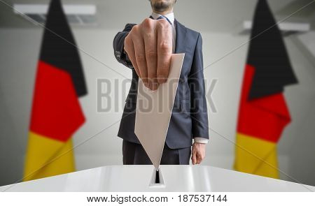 Election or referendum in Germany. Voter holds envelope in hand above ballot. German flags in background. poster