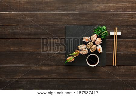 Japanese restaurant, gunkan sushi platter top view on rustic wood background and black slate plates.. Set for two with chopsticks, ginger, soy, wasabi.