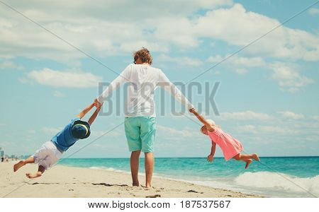 father with little son and daughter play at beach