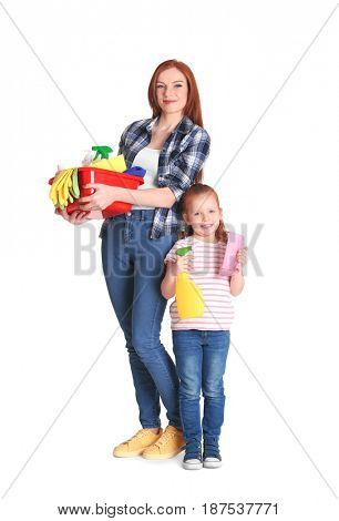 Little girl and her mother with cleaning supplies on white background