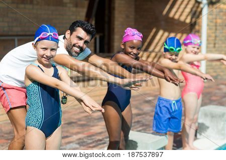 Portrait of male instructor and children preparing for jumping in swimming pool
