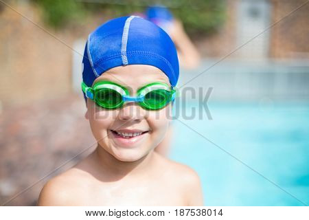 Close up portrait of little boy wearing swimming goggle and cap at poolside