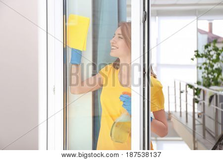 Young woman using detergent and rag while cleaning window in light room