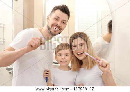 Young couple and their beautiful son brushing teeth near mirror in bathroom