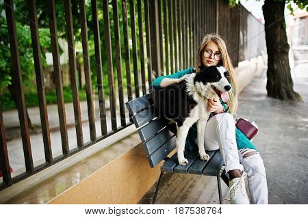 Trendy Girl At Glasses And Ripped Jeans With Russo-european Laika (husky) Dog On A Leash, Against Be