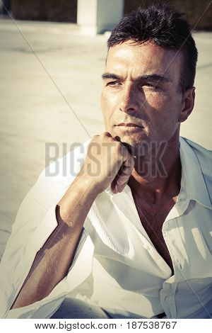 Serious and thinking man. Handsome Italian adult male. Outdoor. Fist under the chin. Intense stare and thoughtfully. White shirt.