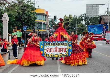 CHIANG MAI THAILAND - AUGUST 24: Young girls and boys in festival costumes parade near the Three Kings Monument on August 24 2016 in Chiang Mai Thailand.