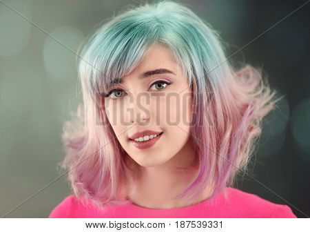 Trendy hairstyle ideas. Young woman with mint hair color on blurred background