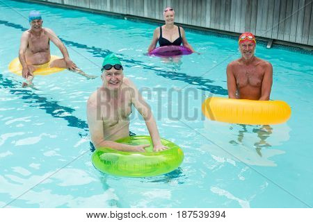 High angle view of seniors swimming with inflatable rings in pool