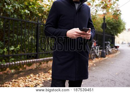 Close Up Of Man Checking Messages On Mobile Phone In Street