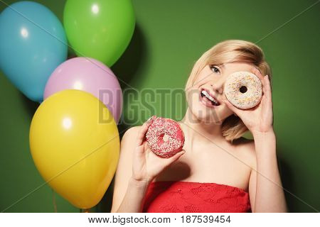 Beautiful woman holding donuts on green background