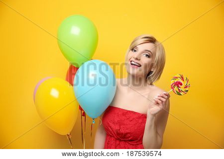 Beautiful woman holding multicolored air balloons and lollipop on yellow background