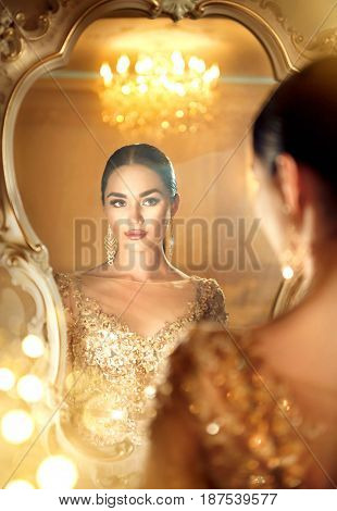 Beauty glamour lady looking in the mirror. Beautiful gorgeous woman in beautiful evening dress in Luxurious style room. Elegant glamorous lady portrait in golden dress