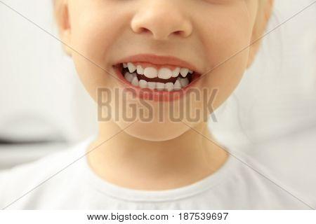 Smiling little child on light background, close up