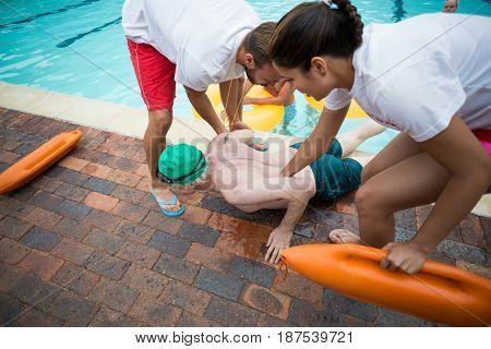 High angle view of male and female lifeguards helping unconscious senior man at poolside
