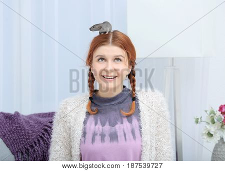 Teenager girl with funny rat at home