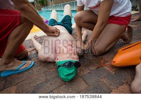 High angle view of lifeguards helping senior man at poolside