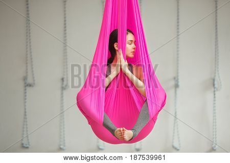 Girl in lotus pose aerial antigravity yoga. Woman sits in pink silk hammock, does exercises, meditate in calm position trying to achieve peaceful state of mind and body