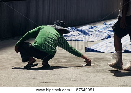 male laborer worker smoothing the cement floor with Concrete Trowel