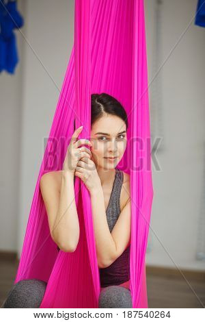 Aerial antigravity yoga concept, relaxed smiling girl in pink silk hammock, woman doing exercises in light studio, meditate in calm position sitting in hanging material