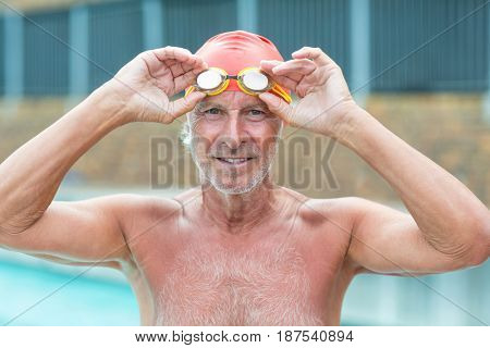 Portrait of senior man holding swimming goggles at poolside