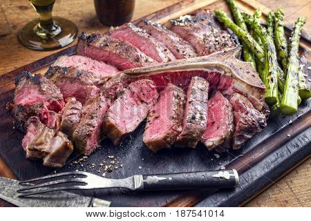 Barbecue dry aged Wagyu Porterhouse Steak sliced with green Asparagus on a cutting board