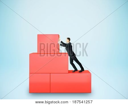 Businessman pushing abstract red blocks on blue background. Stuggle and hard work concept. 3D Rendering
