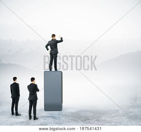 Businessman standing on abstract dark pedestal on landscape background and looking into the distance. Leadership concept