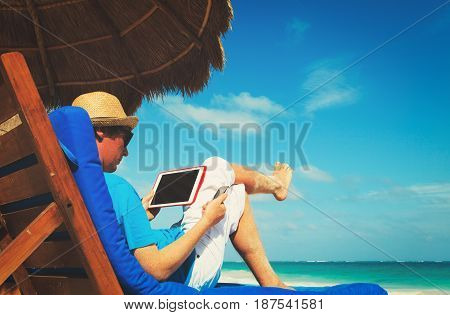 man with touch pad on tropical beach vacation