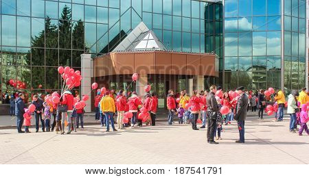 Kirishi, Russia - 9 May, A crowd of people with red balls near the glass facade, 9 May, 2017. Preparation and conduct of the action Immortal regiment in small cities of Russia.
