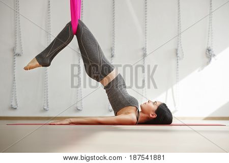 Teenager girl doing stretching with legs fixed in hammock. Aerial yoga exercise or antigravity yoga indoors, woman meditating in sport studio or gym side view