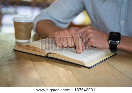 Midsection of young man reading book at table in coffee shop