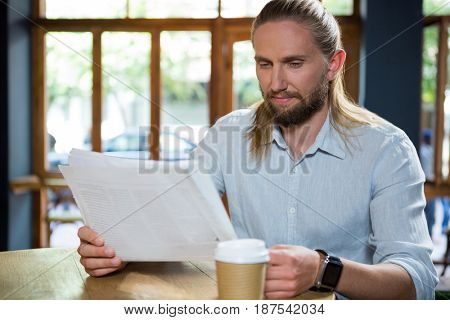 Handsome young man reading newspaper at table in coffee shop