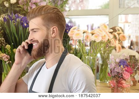 Young handsome florist talking by mobile phone in flower shop