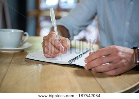 Midsection of young man writing in diary at table in coffee shop