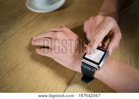 Close-up of man hands using smart watch at table in coffee shop