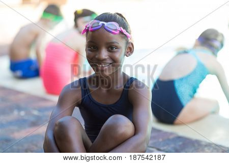 Portrait of happy little girl sitting at poolside